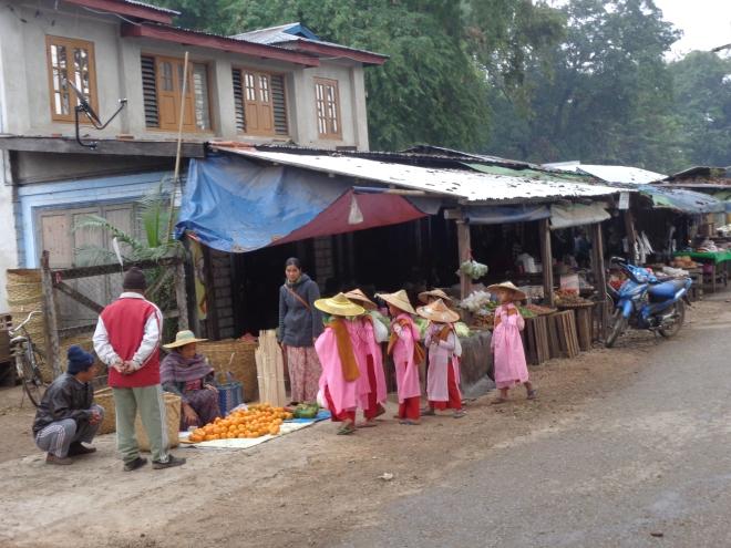 Comme tous les matins, ce groupe de jeunes moines novices, des jeunes filles, viennent récolter l'offrande des marchands...