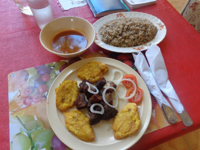Plat de griot (porc grillé) accompagné de bananes pesées, de sauce et de riz.