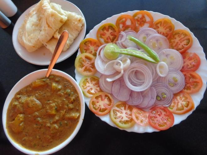 Plat de pommes de terre au curry masala accompagné de chapati et d'une salade de tomates et oignons...