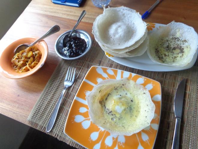 """Pertit déjeuner traditionnel sri lankais. Des """"hoppers"""", galettes de farine de riz, au beurre, accompagnées de pommes de terre et légumes assaisonnés au curry..."""